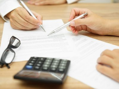 People with letters and a calculator, doing paperwork for a PPI claim.