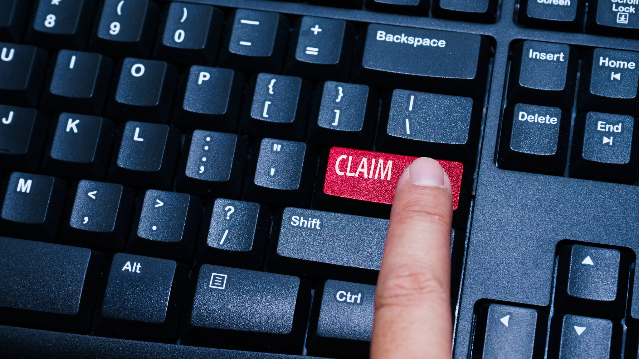 """a keyboard with a user pressing the """"claim"""" key"""