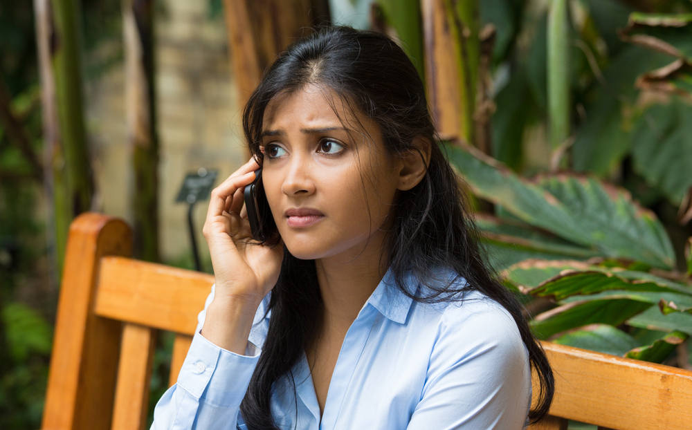 A worried looking woman receiving a PPI phone call