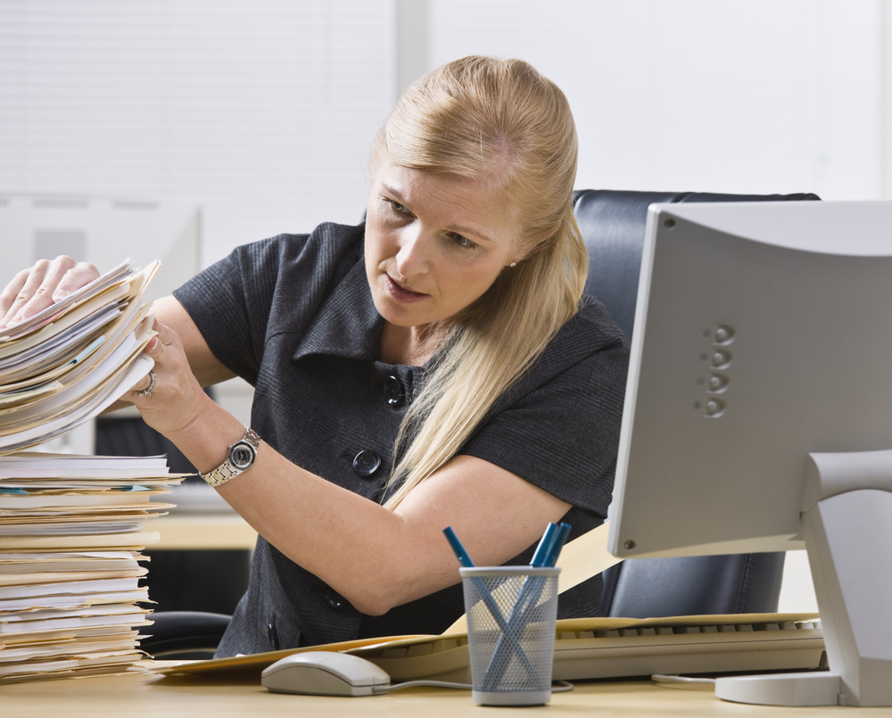 woman looking through a stack of papers for her lost PPI paperwork
