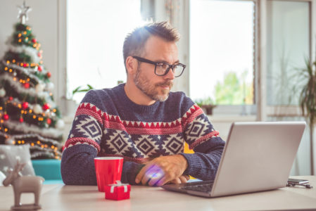man in a Christmas jumper looking at a laptop with a worried expression