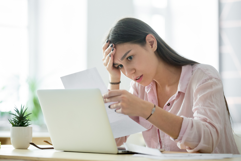 Woman sat at a laptop reading a PPI claim rejection letter
