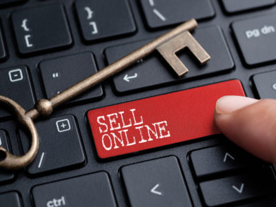 "keyboard with ""sell online"" key and a house key laid on top"