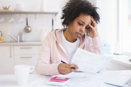a stressed woman looking at bank paperwork